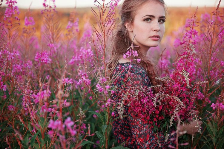 Portrait of beautiful young woman with purple flowering plants