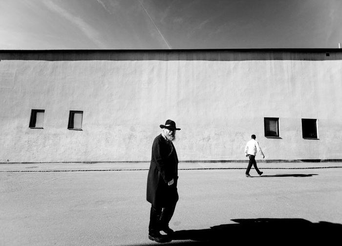 Men walking in city against sky