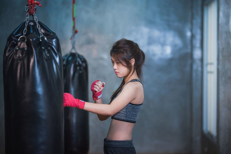 Side view of female boxer punching bag