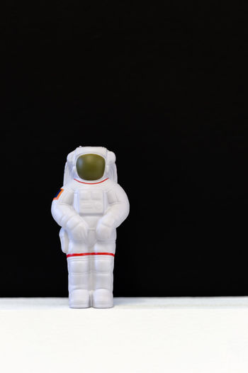 Astronaut soft toy on white floor and black background. Still life macro minimalistic composition. Vertical orientation with text space on right hand side Astronaut Be First Cosmos Human Revolution Science Soft Toy Abyss Aim Astronomy Black Background Concept Contrasting Colors Depths Discovery Education Exploration Human Representation Minimalism Objectives Reach The Goal Space Space Suit Stand Up Technology Universe