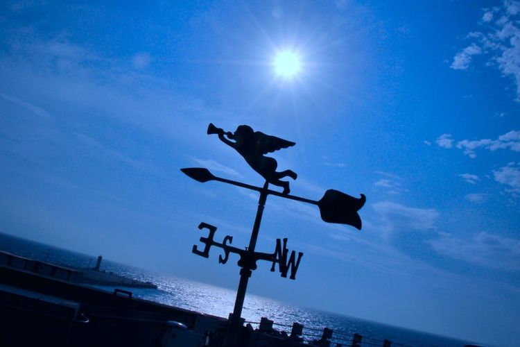 Angel Animal Themes Blue Day Direction Guidance Light And Shadow Low Angle View Nature News No People Outdoors Sea Silhouette Sky Sun Sunlight Water Weather Vane Wind