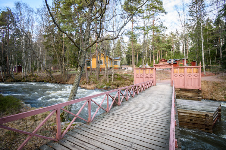 Footbridge over river by trees