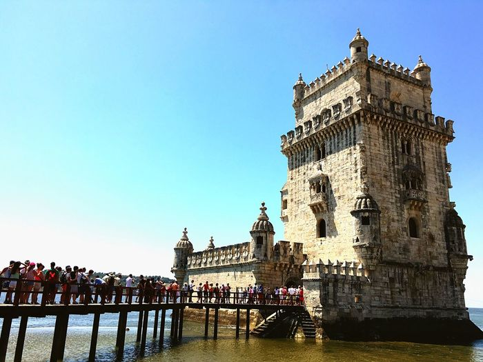 Tourists waiting in line on jetty leading to historic structure