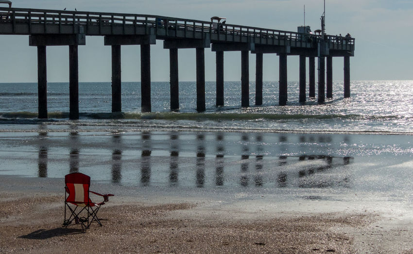 Rear view of pier on beach against sky