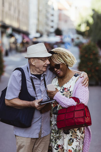 Rear view of man with woman standing on mobile phone