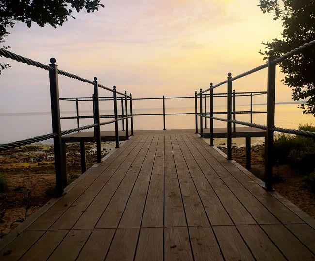 Empty footbridge against sky at sunset