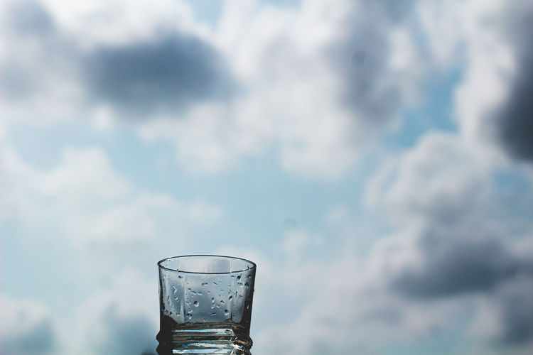 Close-up of drink in water against sky