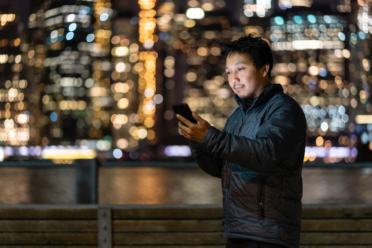 Full length of young man using mobile phone at night