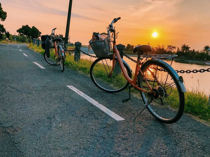 Bicycles on road against sky during sunset