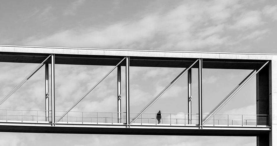 Low Angle View Of Man Walking On Bridge Against Sky