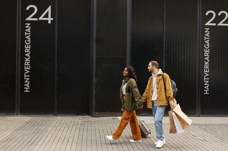 Woman with umbrella walking on footpath