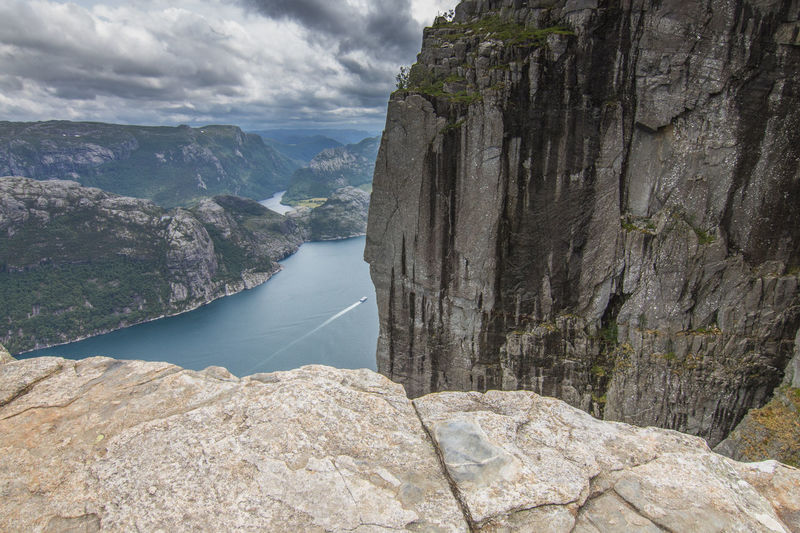 High angle view on water against sky and mountains Lysefjord Beauty In Nature Cliff Cloud - Sky Day Fjord Formation Mountain Mountain Range Nature No People Non-urban Scene Outdoors Rock Rock - Object Rock Formation Scenics - Nature Sky Solid Tranquil Scene Tranquility Water