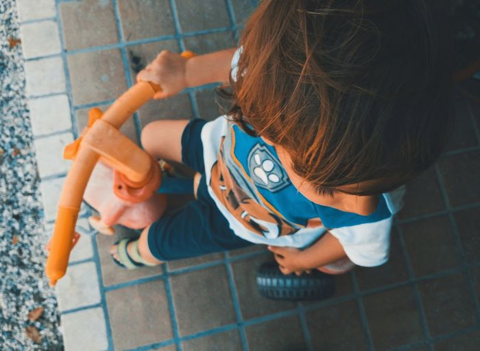 High Angle View Of Boy Sitting On Tricycle
