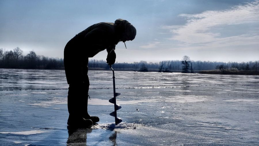 Man drilling in frozen lake against sky during winter