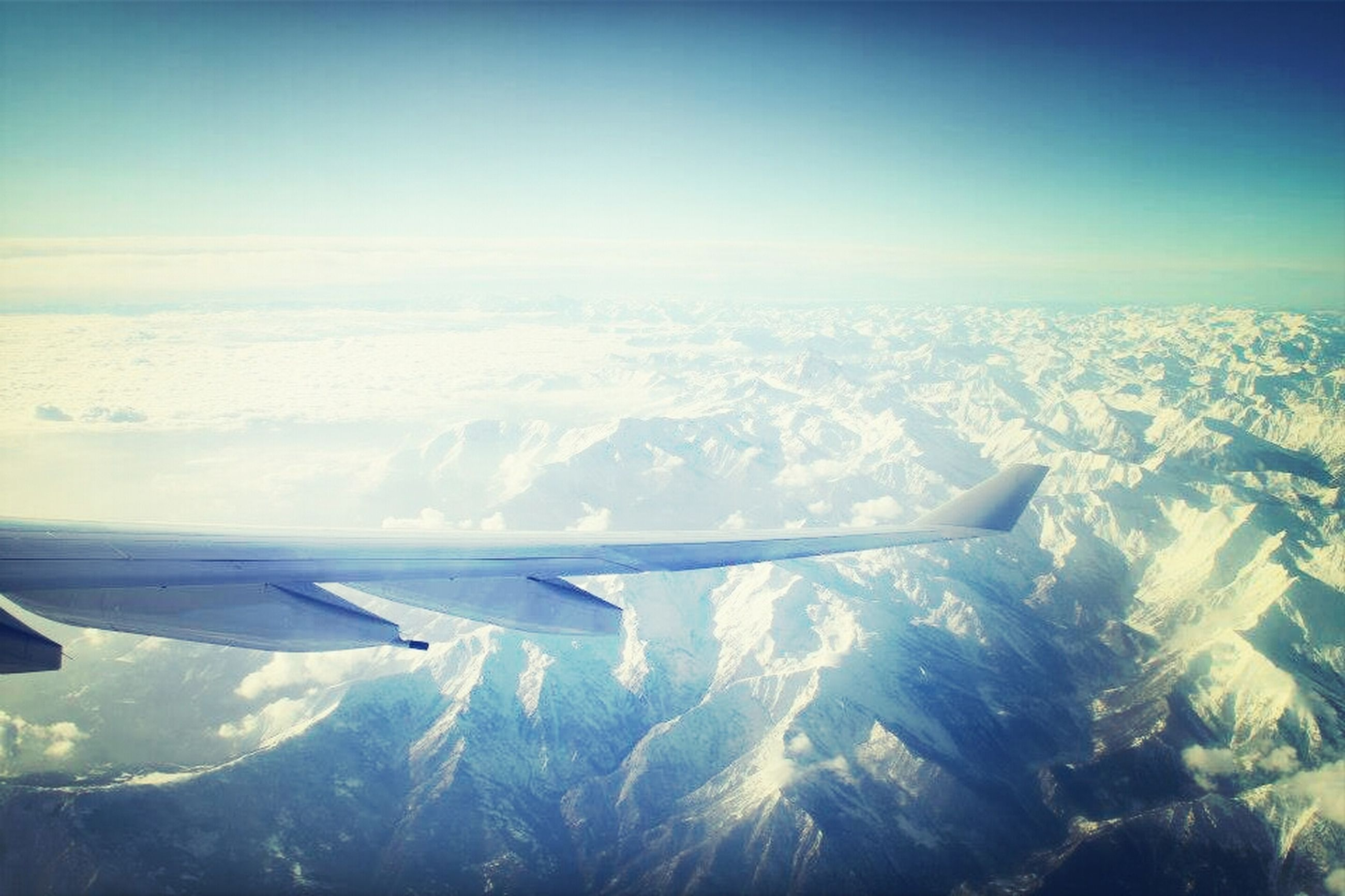 airplane, air vehicle, aircraft wing, aerial view, flying, transportation, snow, winter, mode of transport, cold temperature, landscape, scenics, beauty in nature, part of, travel, nature, cropped, blue, mid-air, snowcapped mountain