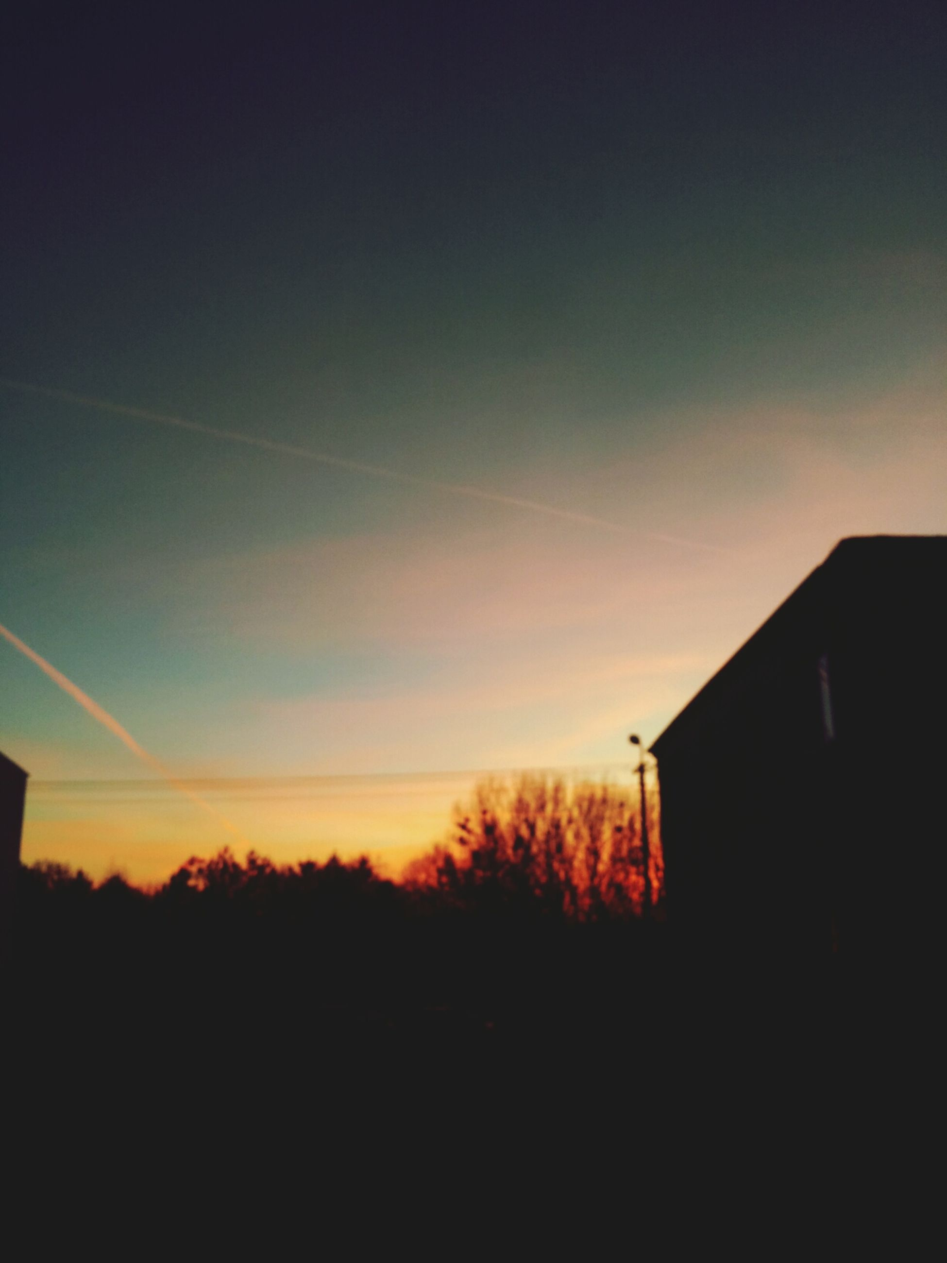 sunset, silhouette, building exterior, built structure, architecture, orange color, house, sky, copy space, tree, beauty in nature, residential structure, nature, scenics, low angle view, dark, outdoors, no people, tranquility, tranquil scene