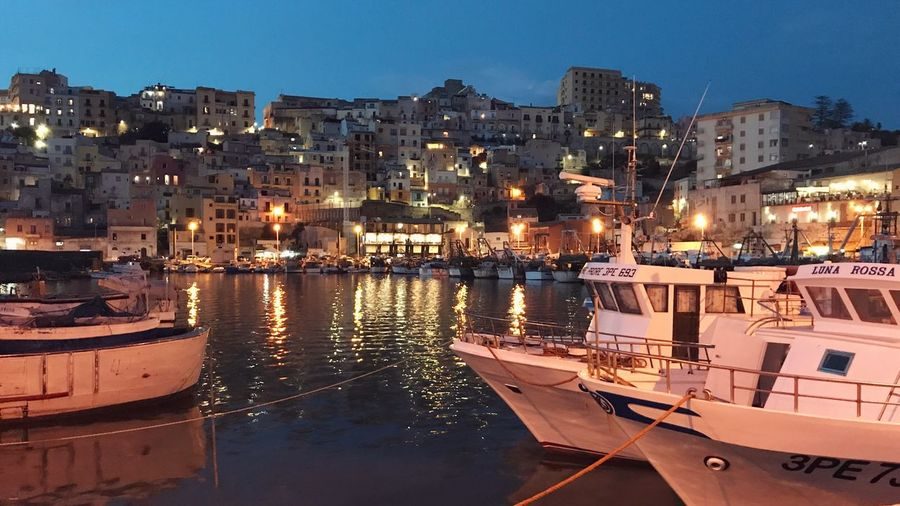 Sailboats moored at harbor by buildings in city at night