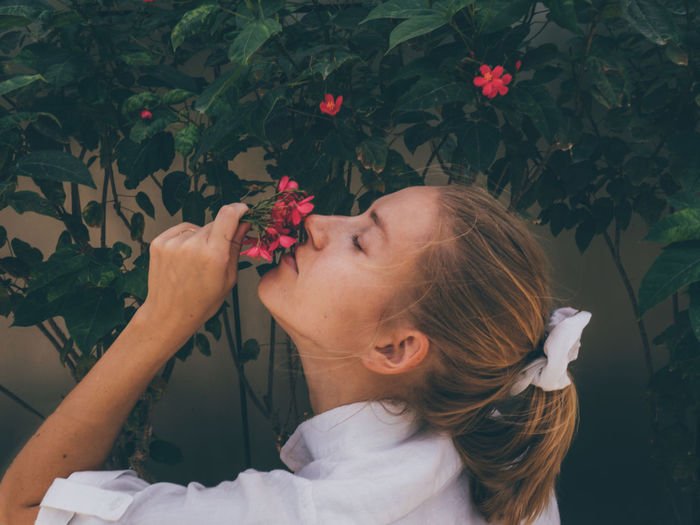 Portrait of woman with pink flowers against plants