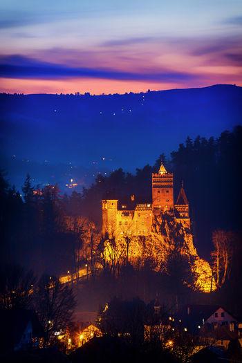 Illuminated bran castle by mountain against sky at dusk