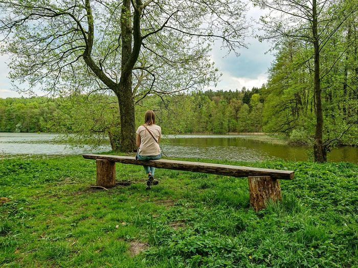 Sitting girl by the lake Lake Mazury Polska Poland Warmia Spring Lakescape Wiosna Europe Warmia-Masuria Masuria Polen Jezioro Springtime Tree Water Full Length Sitting Park - Man Made Space Sky Grass Green Color Bench Lakeside Countryside Green Park Farmland Woods Calm