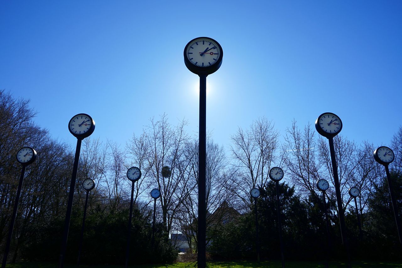 clock, sky, tree, street, time, nature, street light, plant, no people, blue, lighting equipment, low angle view, bare tree, clear sky, dusk, outdoors, pole, day, instrument of time, silhouette, antique, minute hand, clock face