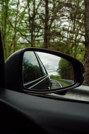 Looking in the side view mirror while driving on a coastal highway. Car Close-up Day Focus On Foreground Glass - Material Land Vehicle Mirror Mode Of Transportation Motor Vehicle Nature No People Outdoors Plant Reflection Road Road Trip Selective Focus Side-view Mirror Transportation Travel Tree Vehicle Interior Vehicle Mirror