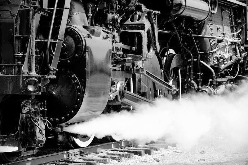 Close-up of steam train leaving smoke on railroad tracks