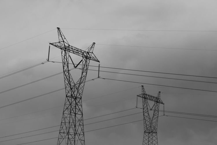 Low angle view of silhouette electricity pylon against cloudy sky