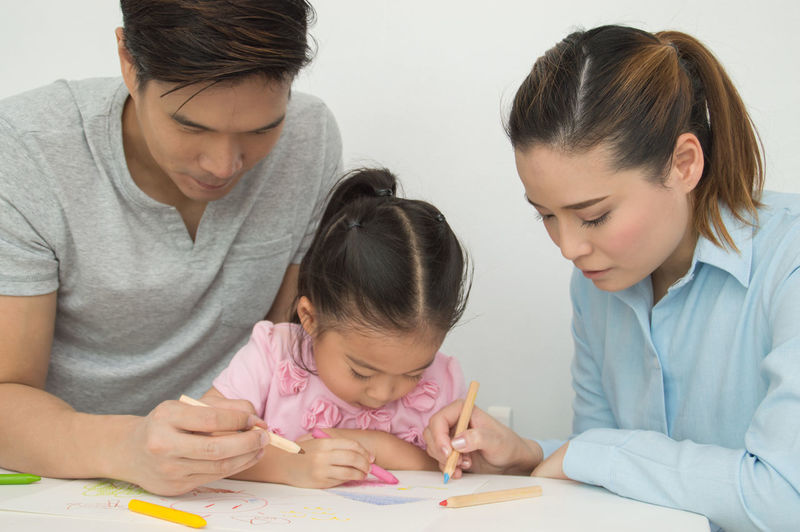 Childhood Child Girls Women Females Family Togetherness Learning Front View Men Art And Craft Group Of People Indoors  Parent Casual Clothing Headshot Sitting Holding Daughter Innocence