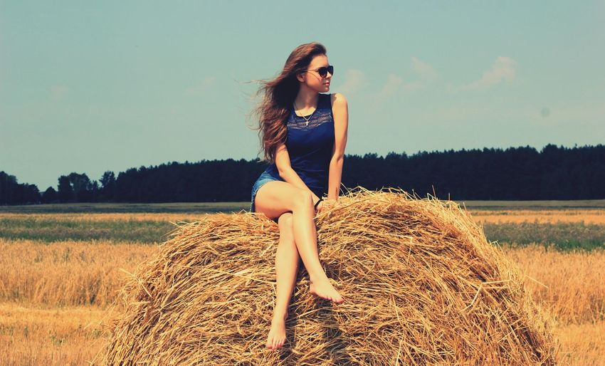 Portrait of young woman on hay bale