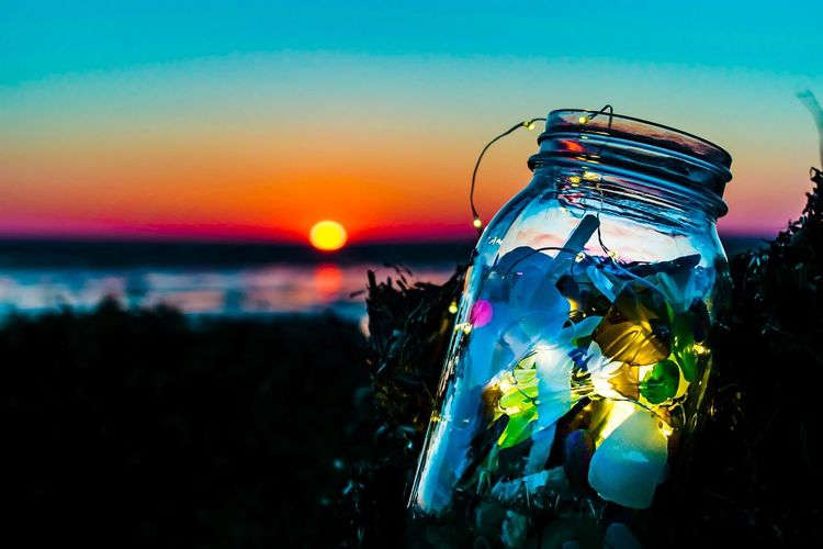 Close-Up Of Lights In Jar During Sunset