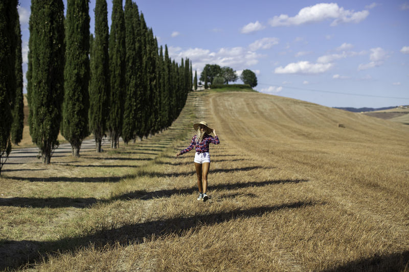 Full length of woman walking on field against sky