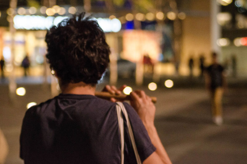 Rear view of man playing flute on street in city at night