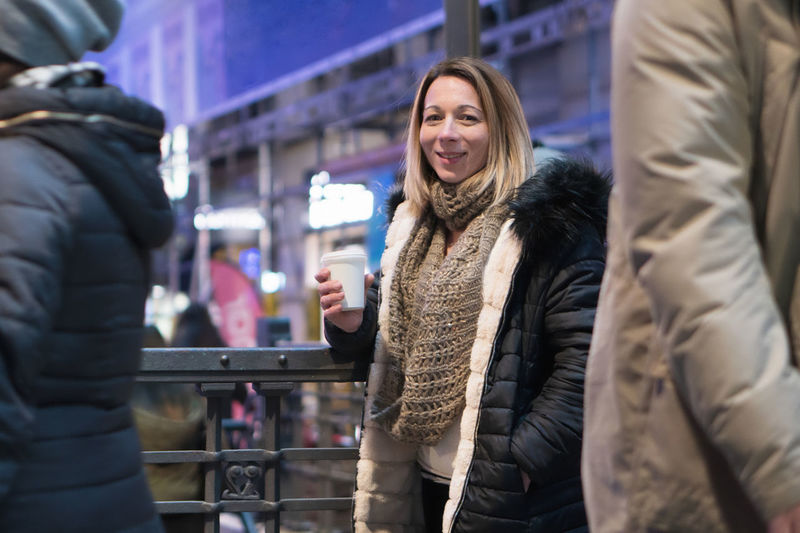 Portrait of smiling woman holding coffee standing outdoors