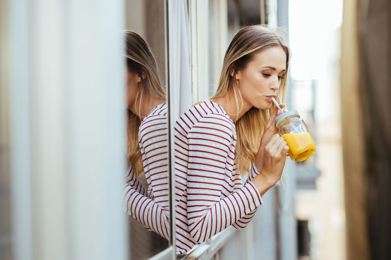 Young woman drinking juice while leaning out of window