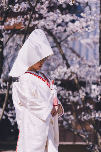 Midsection of woman holding cherry blossom