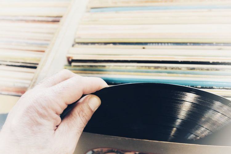 Cropped hand of man removing record from box