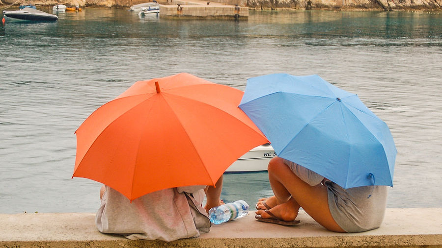Urlaub mit Regenschirm - rainy weather Hafenmauer Rain Beach Lifestyles Low Section Nature Outdoors People Rainy Holiday Real People Regen Relaxing Moments Sea Sitting On A Wall Talking Beachlife Two People Umbrellas Women The Week On EyeEm Best Shots Hofi Hofis Premium Collection