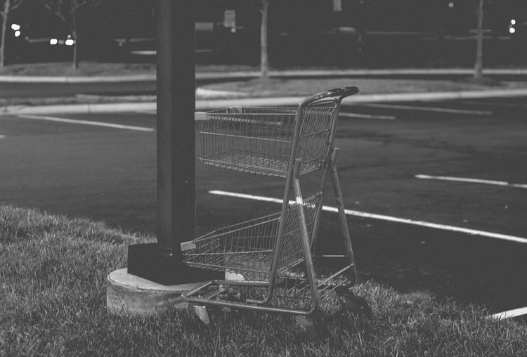 Empty shopping cart on field by road