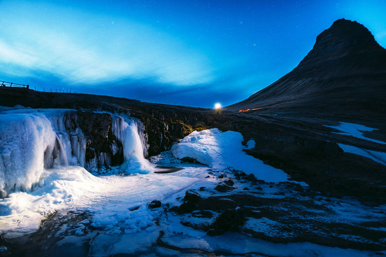 There is something incredible in a frozen waterfall... Find more travel inspiration at http://www.instagram.com/simonmigaj Iceland Kirkjufell Astrophotography Beauty In Nature Blue Cold Temperature Environment Flowing Flowing Water Headtorch Landscape Mountain Mountains Nature Night Power In Nature Scenics - Nature Sky Snow Snowcapped Mountain Torch Tranquility Water Waterfall Winter