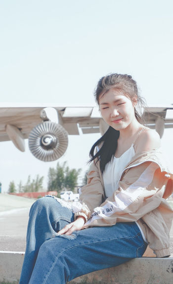 Smiling young woman sitting against sky