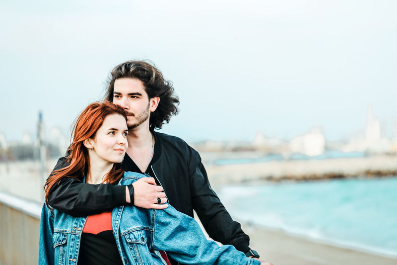 Happy young couple enjoying sea view on a warm spring day. Handsome man gently hugs his beautiful red-haired beloved. Two People Young Adult Lifestyles Portrait Real People Young Women Togetherness Couple - Relationship Positive Emotion Love Couple Young Couple In Love Together Springtime Sea Beach Leisure Activity Focus On Foreground Water Bonding Women Young Men Adult Casual Clothing Day Standing People Outdoors Beautiful Woman Scarf My Best Photo The Portraitist - 2019 EyeEm Awards