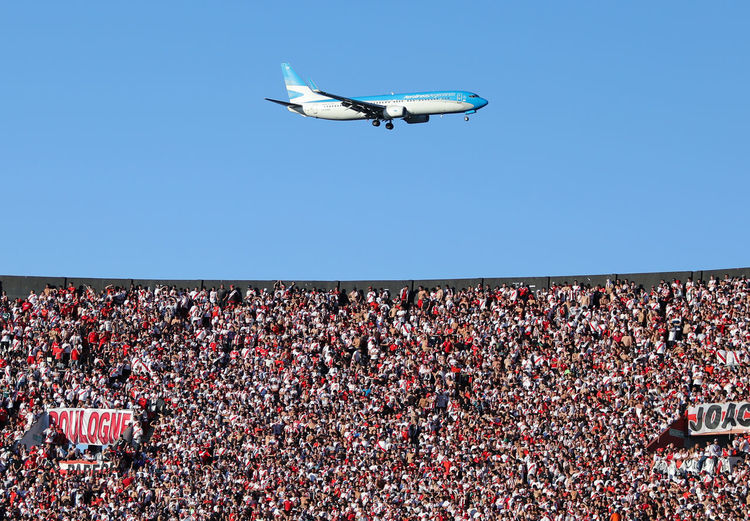 Flying Sky Clear Sky Blue Mid-air Crowd Air Vehicle Airplane Day Mode Of Transportation Low Angle View Group Of People Real People Nature Transportation Outdoors Sport Spectator Stadium