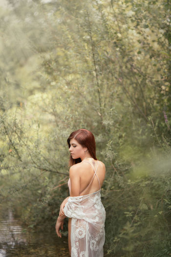 Rear view of beautiful woman standing against trees