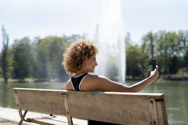 Young woman using mobile phone while sitting on seat
