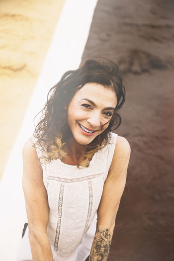 Portrait of smiling mature woman against wall