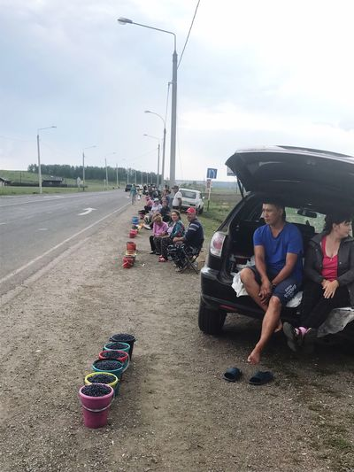 Real People Transportation Car Men Land Vehicle Day Mode Of Transport Sky Road Cloud - Sky Women Standing Sitting Full Length Lifestyles Outdoors Technology Young Adult Adult People