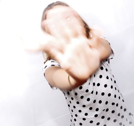Woman Shielding Face Against White Background