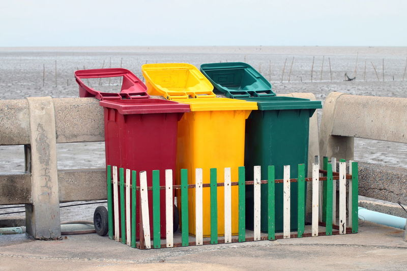 Multi colored garbage bins by railing