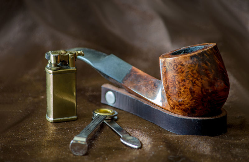Close-up of smoking pipe by cigarette lighter on brown leather